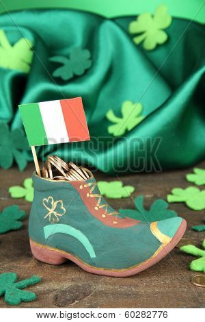 Saint Patrick day boot with gold coins and clover leaves on green background