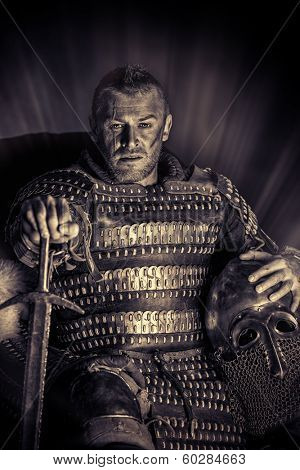 Portrait of a courageous ancient warrior in armor with sword and shield. Black-and-white photo.