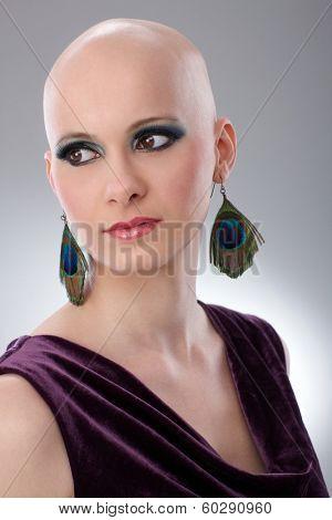 Studio portrait of bald woman wearing elegant claret velvet dress.