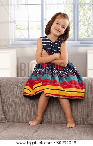 Cute little girl sitting on backrest of sofa, smiling, arms crossed.
