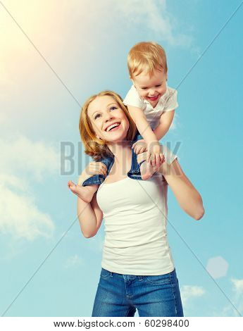 Baby Sits Astride The Shoulders Of The Mother And Laughing On Blue Sky