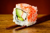 stock photo of chopsticks  - Japanese food roll sushi closeup detail on chopsticks - JPG