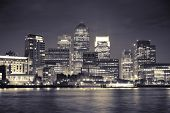 stock photo of canary  - Canary Wharf business district in London at night over Thames River - JPG