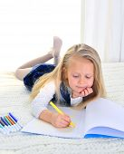 Adorable Blonde Little Girl On Bed Drawing With Markers