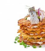 Fried potato pancakes with herring on white background
