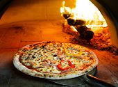 pic of oven  - Close up pizza in firewood oven with flame behind - JPG