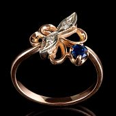 Vintage golden ring with diamonds and sapphire isolated on black