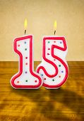 Burning birthday candles number 15 on a wooden background
