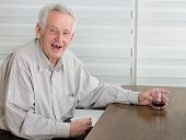 stock photo of laugh out loud  - Old man holding glass with alcohol dring and laughing laudly - JPG