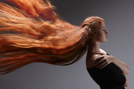 foto of hair motion  - Beautiful red headed woman with long hair flying against gray background - JPG