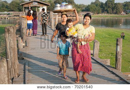 MANDALAY, MYANMAR - JAN 19, 2014: Unidentified local citizens of Amarapura crossing U Bein bridge located on Taungthaman Lake. Bridge is believed to be the oldest and longest teak bridge in the world