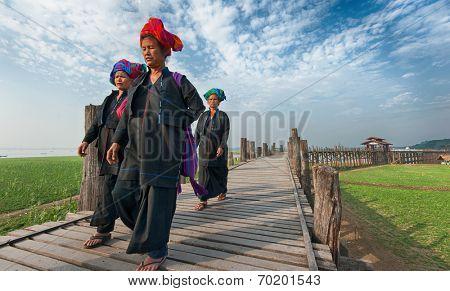 MANDALAY, MYANMAR - JAN 19, 2014: Unidentified women from hill tribe minority of Burma in traditional clothes crossing U Bein teak wooden bridge - famous Burmese landmark.