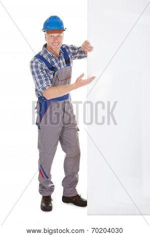 Confident Manual Worker Holding Billboard