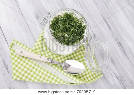 Glass round bowl of cream with a tuft of dill and pepper near it on a napkin on wooden background