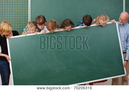 Young Students And Teachers Holding A Blackboard