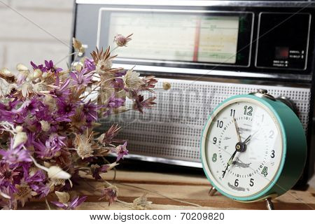 Retro radio, clock and flowers on table in room