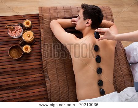 Hand Placing Lastone On Man's Back In Spa