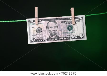 Dollar bills hanging on rope attached with clothes pins. Money-laundering concept. On dark color background