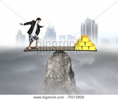 Businessman Stands On Rocky Seesaw Vs Stack Of Gold
