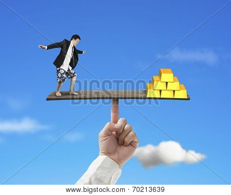 Man Standing On Finger Seesaw Vs Stack Of Gold