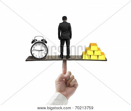 Standing Man Between Clock And Gold Balancing On Finger Seesaw