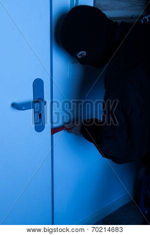 Thief Opening House Door With Crowbar