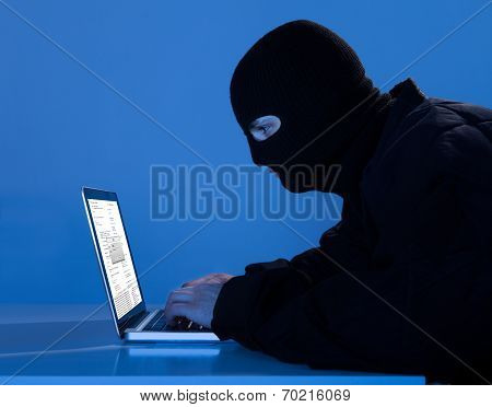 Criminal Using Laptop To Hack Data At Table