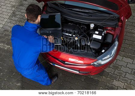Mechanic Using Laptop While Repairing Car