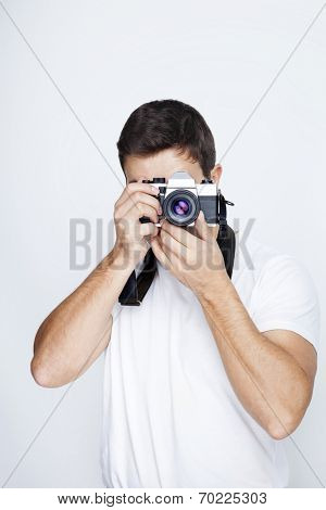 Young man using a retro camera against gray background