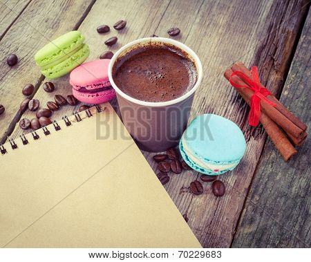 Macaroons, Espresso Coffee Cup, Cinnamon Sticks And Sketch Book On Wooden Rustic Table