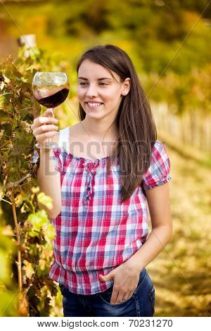 Young woman with glass of wine in the vineyard, tasting wine