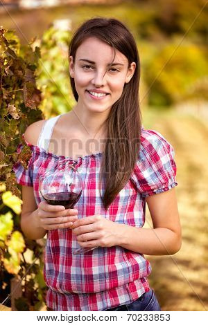 smiling woman wine tasting in the vineyard