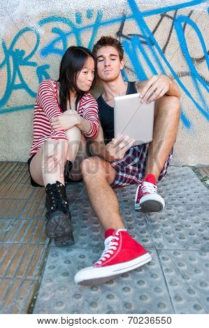 Young Multi-ethnic Couple Using A Tablet Pc.