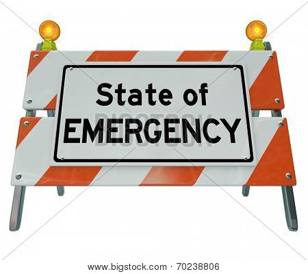 State of Emergency words on a road construction barricade or warning sign illustrating a dangerous crisis, problem or disaster is ahead