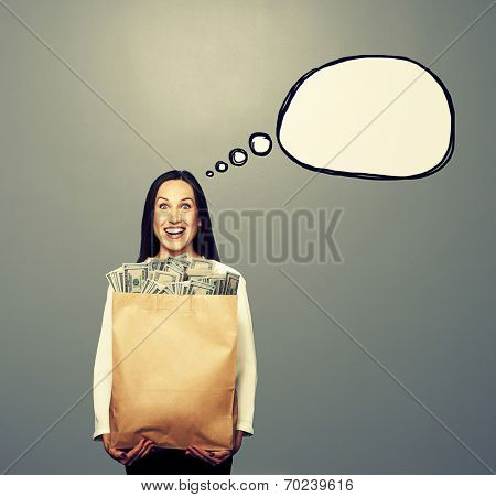 excited young woman holding paper bag with money. concept photo with drawing speech bubble over grey background