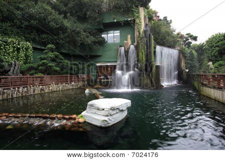 a chinese restaurant with waterfall outside