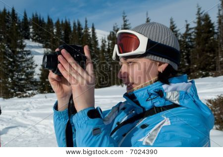 Photographer In Snow Mountains