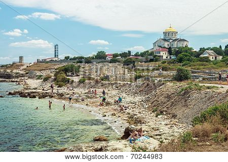 Tourists Basking On A Wild Beach Of The Ancient City Of Chersonesos