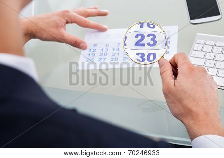 Businessman Looking At Calendar Through Magnifying Glass