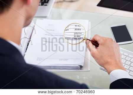 Auditor Examining Invoice With Magnifier