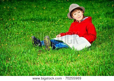 Cute 7 years old boy sitting on a grass with a book. Summer day.