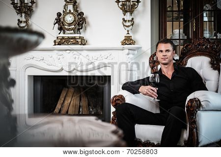 Handsome well-dressed man sitting with red wine in luxury  house interior