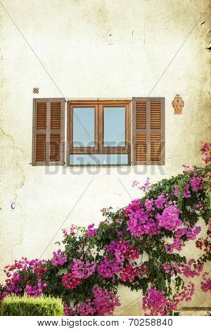 Catalan window with open wooden shutters, decorated with pink flowers