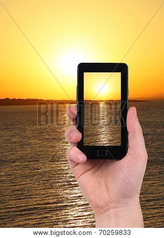 Taking sunset photo on smartphone.