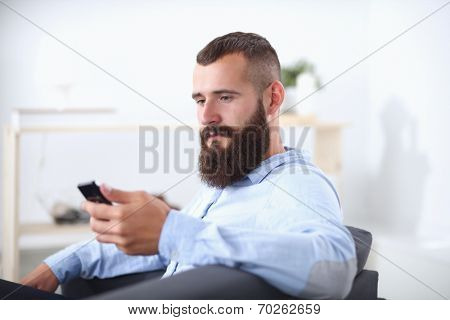 Businessman sitting the sofa in office lobby with phone, isolat