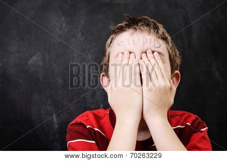 Boy with Stupid written on his forehead