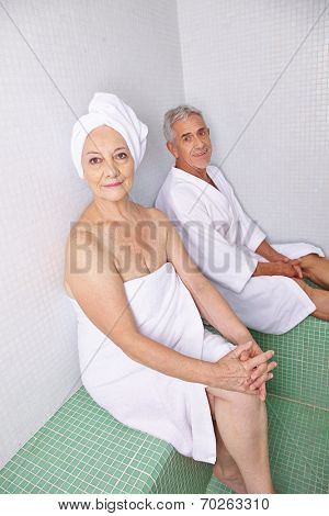 Old woman and man relaxing after sauna session in a spa