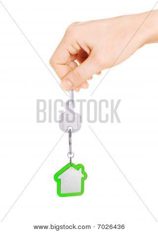 Hand holding key of house