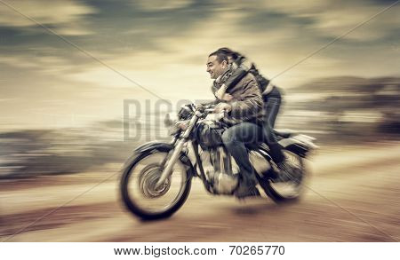 Two happy people riding on motorcycle, slow motion effect, grunge style photo, romantic relationship, speed and adventure concept