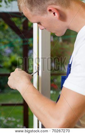 Man Repairing Window Frame